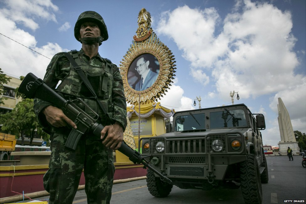 A Thai soldier stands in front of a portrait of Thai King Bhumibol Adulyadej as he patrols near government buildings in Bangkok - 23 May 2014
