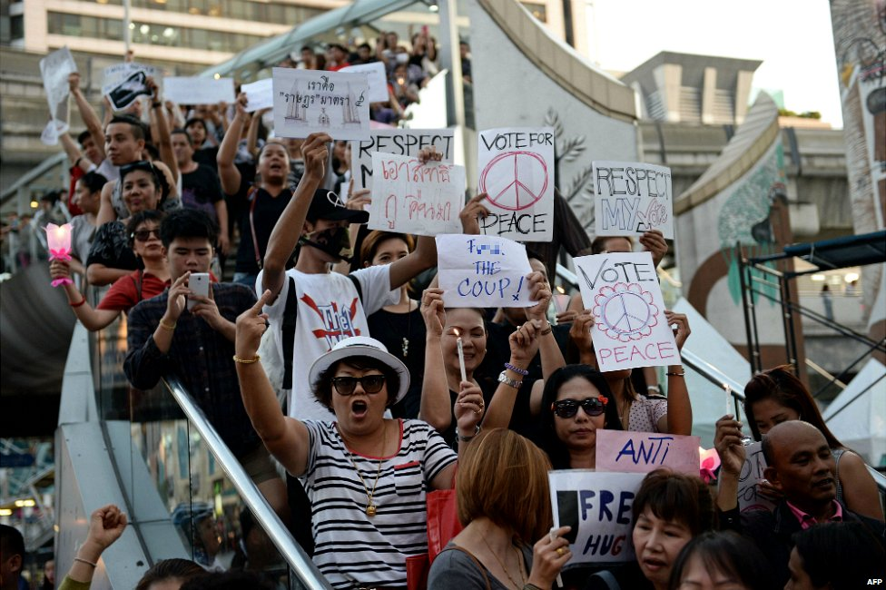 Anti-coup activists hold signs as they gather to protest against the actions of the Thai army in downtown Bangkok - 23 May 2014