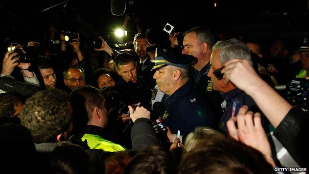 Boston Police Commissioner Edward Davis is surrounded by reporters during a press conference following the Boston Marathon bombings.