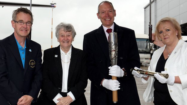 - The baton with Chris Jenkins, CEO of Commonwealth Games Wales, Anne Ellis, President of Commonwealth Games Wales, John Griffiths, Minister for Culture and Sport and Helen Phillips, Chair of Commonwealth Games Wales