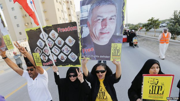 "Protesters hold banners with photo of Nabeel Rajab asking for their release in Al A""ali south of Manama, on 18 April2014."