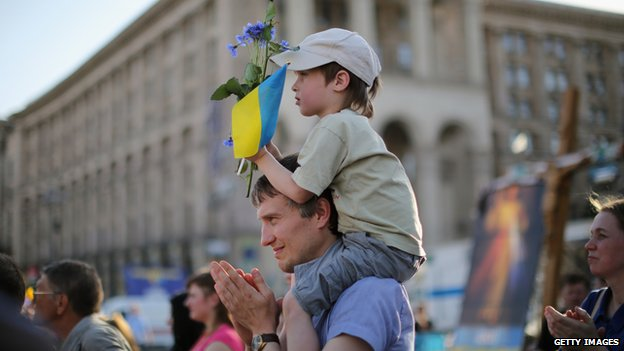 "A young boy holds a flower and a Ukrainian flag as a ""flash mob"" sing traditional Ukrainian songs and pray for a peaceful election, in Kiev on 24 May 2014"