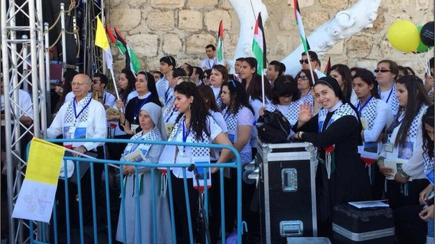A nun and her charges wait for the Pope to arrive in Manger Square in Bethlehem