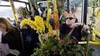 Gardening enthusiasts sit on a bus with their discounted purchases from the final day of the Chelsea Flower show