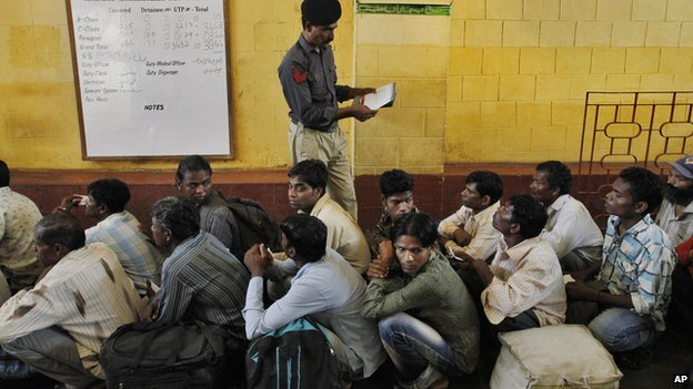 A Pakistani police officer checks the documents of an Indian fishermen waiting for their release from a prison in Karachi on 25 May 2014.
