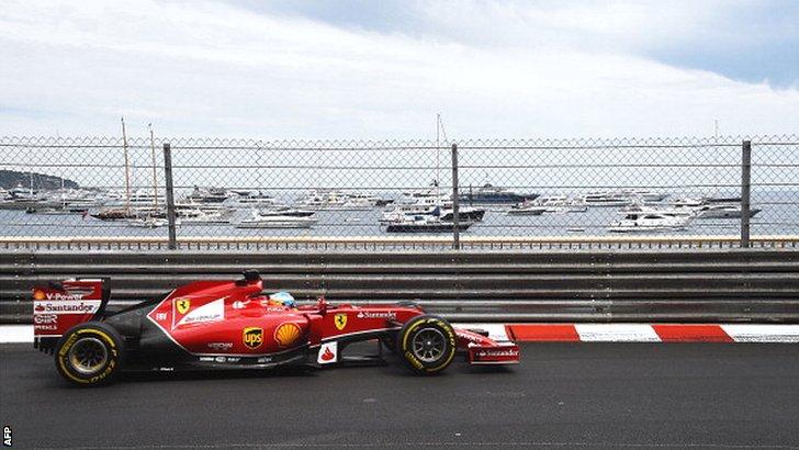 Fernando Alonso drives past the marina