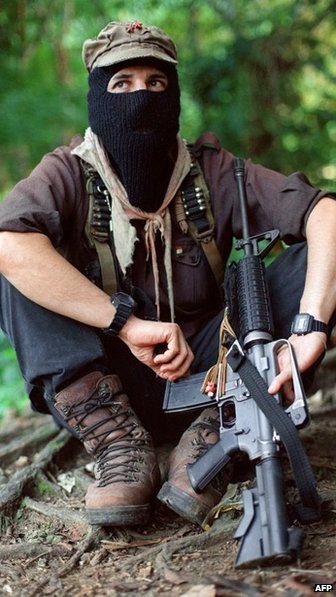 Subcomandante Marcos wears his trademark ski mask and holds an assault rifle in Chiapas, August 20, 1997.