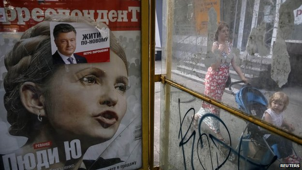 A woman pushes her child on a pram past an advertisement of a magazine cover of former prime minister and presidential candidate Yulia Tymoshenko and an election poster for businessman, politician and presidential candidate Petro Poroshenko, a day after Ukrainian presidential elections, in Kiev May 26, 2014.