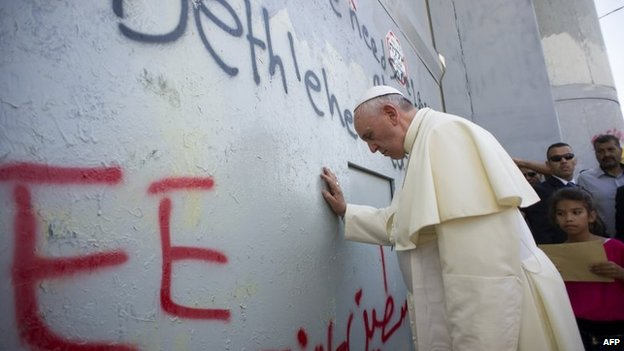 Pope Francis prays outside a section of the Israeli security barrier in the West Bank near Bethlehem