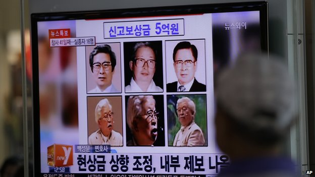 A man watches a TV news program on the reward poster of Yoo Byung-eun at the Seoul Train Station in Seoul, South Korea, Monday, May 26, 2014.