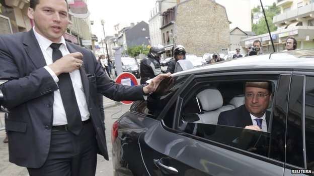 France's President Francois Hollande sits in his car