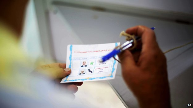 A voter holds his ballot in the Egyptian presidential election on 26 May 2014