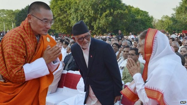Bhutanese Prime Minister Tshering Tobgay (L) greets former Indian president Pratibha Patil (R) as Nepalese Prime Minister Sushil Koirala (C) looks on during the swearing-in ceremony for Indian prime minister-designate Narendra Modi in New Delhi on May 26, 2014