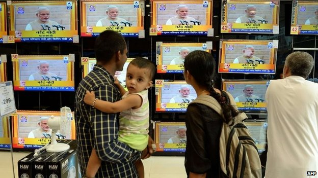 "Residents watch a bank of televisions featuring images of Narendra Modi taking his oath as India""s Prime Minister in New Delhi at a multi brand electronic showroom in Mumbai on on May 26, 2014"