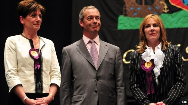 UK Independence Party (UKIP) leader Nigel Farage (C) stands on stage after being re-elected as an MEP flanked by fellow UKIP MEPs Janice Atkinson (R) and Diane James (L) (25 May 2016)