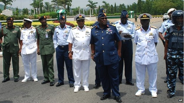 Chief of Defence Staff Air Marshal Alex Badeh, front, and other military chiefs wait to address protesters in Abuja, Nigeria - 26 May 2014