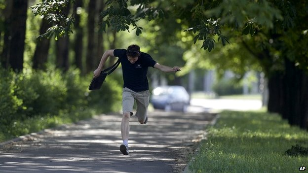 A local resident runs for cover during fighting near Donetsk airport - 26 May 2014
