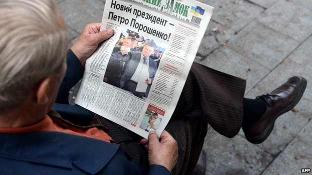 A man reads a newspaper with the picture on the front page depicting Ppesidential candidate Petro Poroshenko - 26 May 2014