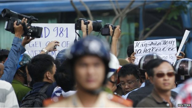 "Police and security personnel film protesters holding placards which read, ""Haiyang 981 oil rig get out of Vietnam (L)"" and ""Take China to the international court"" (R) as they march during an anti-China protest in Vietnam's southern Ho Chi Minh city May 18, 2014. Vietnam flooded major cities with police to avert anti-China protests on Sunday in the wake of rare and deadly rioting in industrial parks that deepened a tense standoff with Beijing over sovereignty in the South China Sea. Several arrests were made in the capital Hanoi and commercial hub Ho Chi Minh City within minutes of groups trying to start protests, according to witnesses, as Vietnam's communist rulers stuck to their vow to thwart any repeat of last week's violence in three provinces in the south and centre"