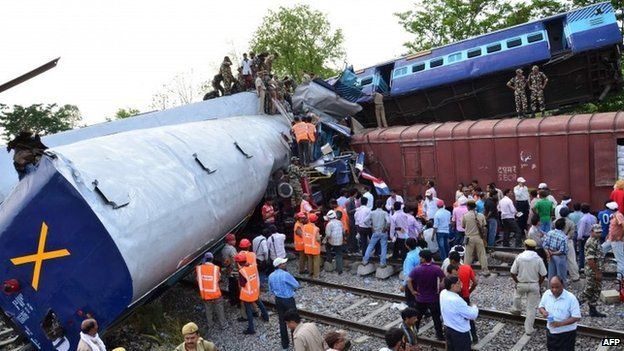 Indian officials and rescuers stand near the wreckage after the Gorakhpur Express passenger train slammed into a parked freight train at Chureb in Uttar Pradesh state, Monday, May 26, 2014.