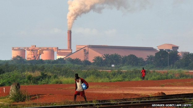 A man walks on rail track near the bauxite factory of Guinea's largest mining firm, Compagnie des Bauxites de Guinee.