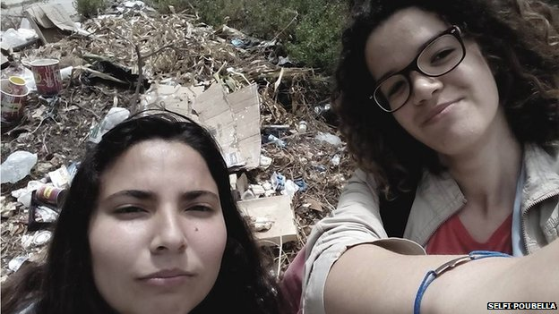 Two girls pose in front of a pile of rubbish