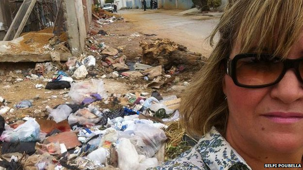 A woman poses in front of a pile of rubbish