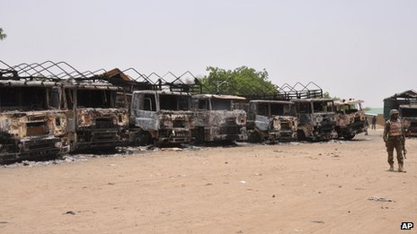 In this photo taken Sunday May 11, 2014, a soldier stands guard in front of burnt trucks following an attack by Islamic militants in Gambaru, Nigeria.