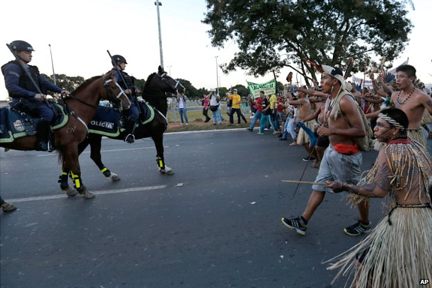 Indigenous protesters approach police during a protest against the football World Cup in Brasilia - 27 May 2014