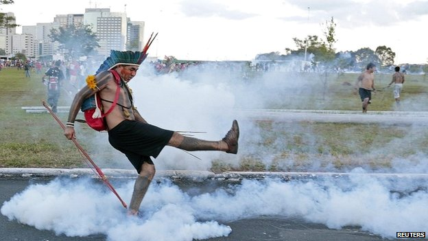 A native Brazilian kicks a tear gas grenade back at riot police in Brasilia - 27 May 2014