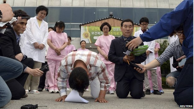 Officials kneel and bow as they apologise to victims outside a hospital in Jangseong, southwest region of Jeolla on 28 May.