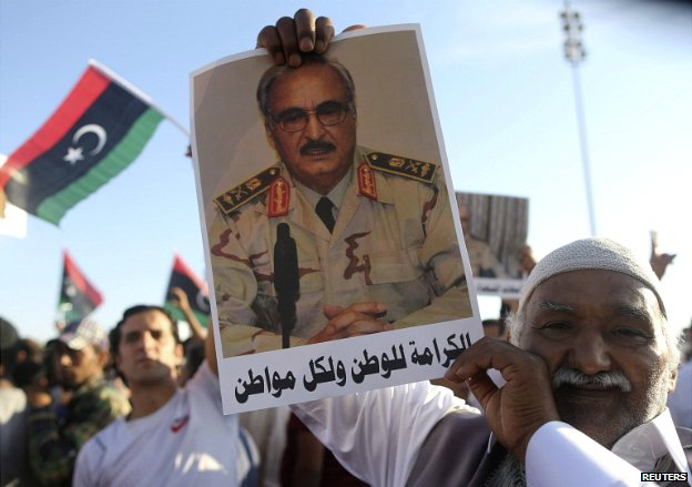 A man holds a picture of General Khalifa Haftar during a show of support in Benghazi - 23 May 2014