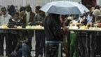 Migrants try to shelter from heavy rain during the daily food distribution at the harbour in Calais