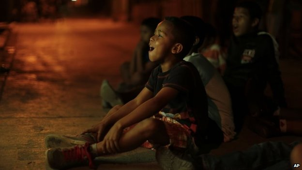 Children watch a friendly match between Honduras and Venezuela on TV on 5 March 2014