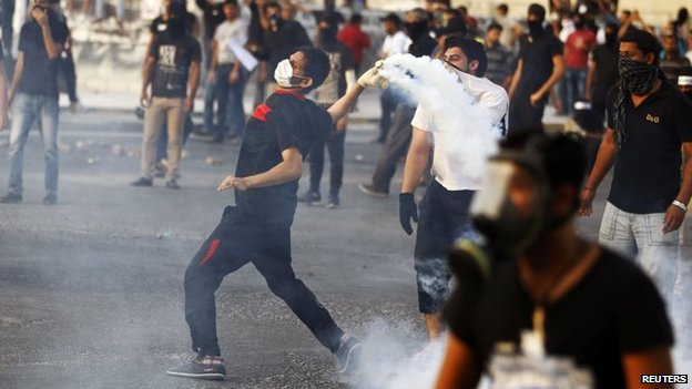 Anti-government protester throws a tear-gas canister at police at a protest in Sitra (27 May 2014)