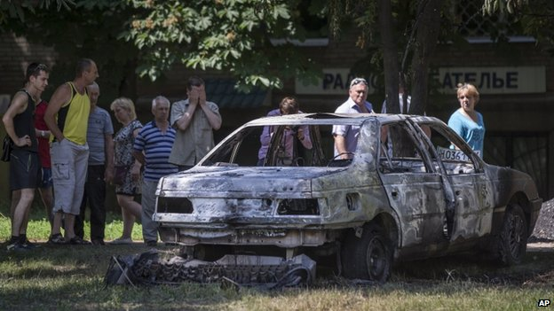 Local people look at a burnt-out car following a shelling from Ukrainian government forces, in Sloviansk
