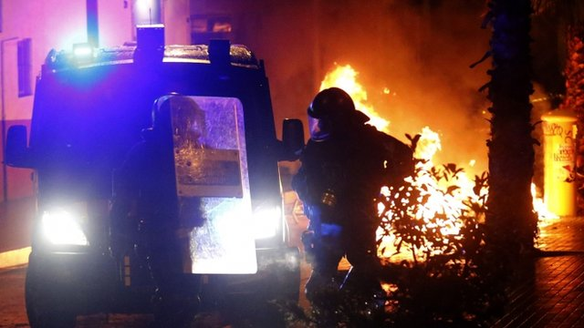 Police stand near burning containers during a protest against the eviction of squatters from the Can Vies building in the Sants neighbourhood of Barcelona