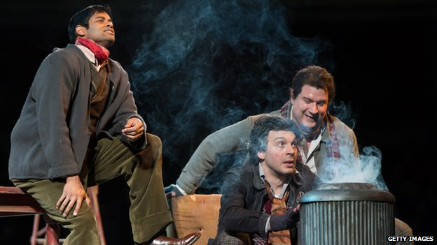 Characters in La Boheme, gathered around a brazier