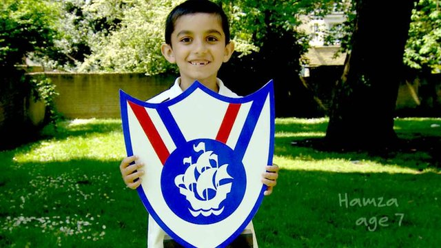 A seven year old boy holding up a large cut out of the Blue Peter Sport badge