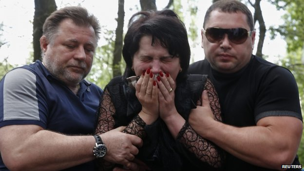 A grieving woman is being supported by two men near the coffin of a taxi driver shot in clashes near Donetsk airport (29 May 2014)