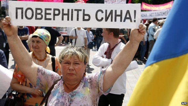 "A Ukrainian woman holds up a banner reading ""bring back my son"" at a rally with other relatives of Ukrainian officers and soldiers in Kiev (29 May 2014)"