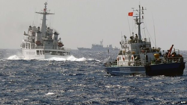 File photo: A China Coast Guard ship (left) blocks the way of a Vietnam Coast Guard ship near to the site of a Chinese drilling oil rig (right, background) being installed at the disputed water in the South China Sea, 14 May 2014