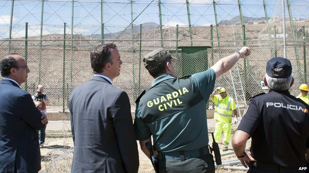 Spanish Secretary of State for Security Francisco Martinez Vazquez (2ndL) listens to a Spanish civil guard following a morning assault at the border in Melilla, on May 28