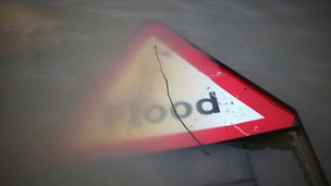 Flood sign partly submerged in water.