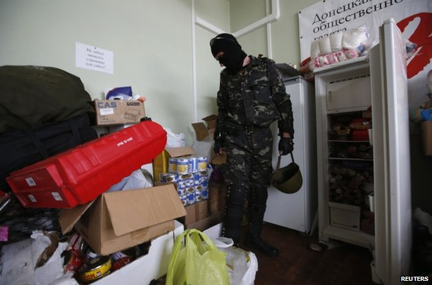 A Vostok fighter shows looted goods he says were looted in Donetsk, 29 May
