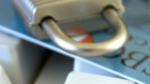 Padlock and credit card on computer keyboard