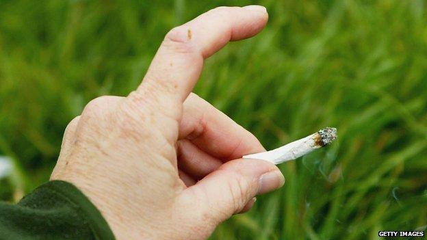 Hand holding cannabis cigarette