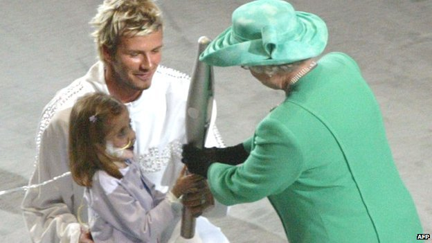 David Beckham and Kirsty Howard hand the Queen's Baton to the Queen.