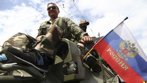Vostok fighters aboard a troop carrier with a Russian flag in Donetsk, 25 May