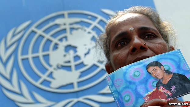 A Sri Lankan demonstrator holds a portrait of a missing relative